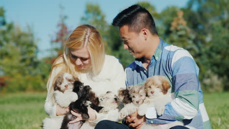 Young-Couple-Holding-Litter-of-Puppies