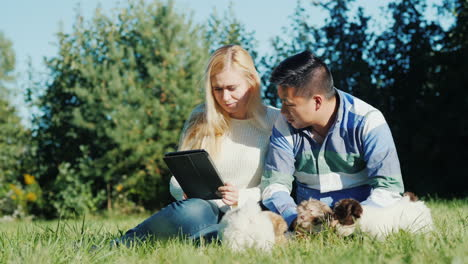 Couple-With-Puppies-and-Tablet-in-Backyard