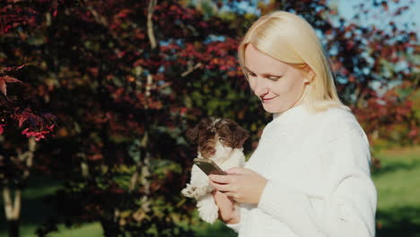 Woman-Holding-Puppy-Uses-Phone
