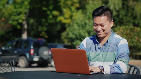 Happy-Man-Working-On-Laptop-Outdoors