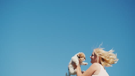 Woman-Jumping-With-Puppy-Against-Blue-Sky