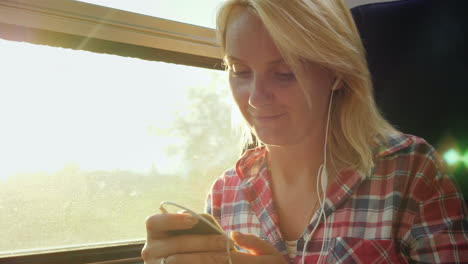Young-Woman-On-A-Train-Using-A-Cellphone