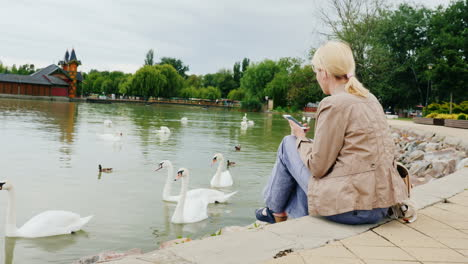 Woman-With-Phone-Feeding-Swans