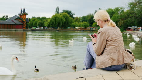 Woman-Uses-Phone-by-Water