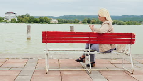 Woman-On-A-Bench-Uses-Phone