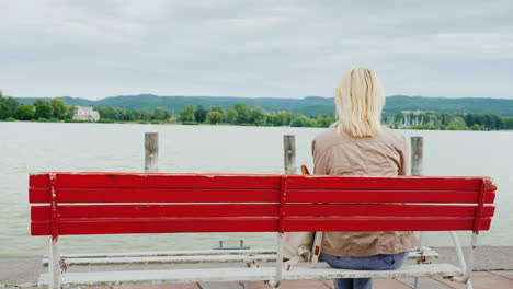 Woman-on-Red-Bench-Admires-a-Lake