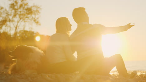 Young-Couple-and-Dog-at-Sunset