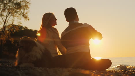 Happy-Couple-and-Dog-at-Sunset