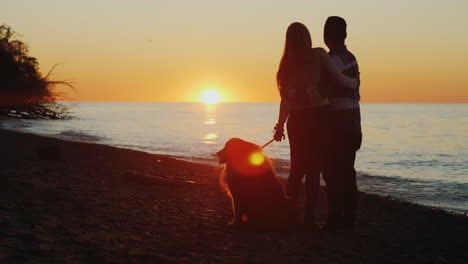 Couple-and-Dog-Watch-Sunset-by-a-Lake
