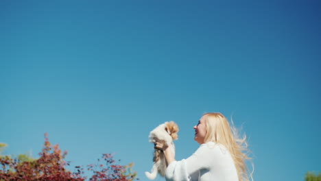 Young-Woman-Holding-Puppy-Jumping