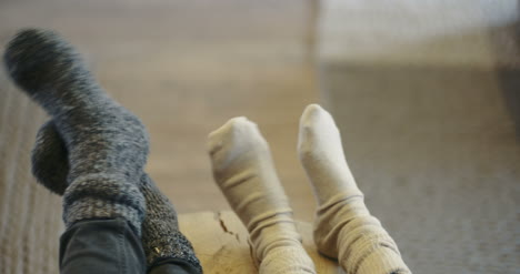 Young-Couple-Wearing-Socks-At-Home