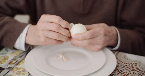 Old-Man-Peeling-Egg-On-Plate-2