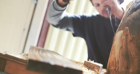 Close-Up-Of-Carpenter-Shaping-Wood-With-Chisel