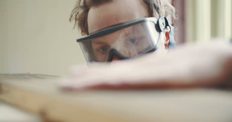 Carpenter-In-Protective-Glasses-Checking-Wooden-Board-