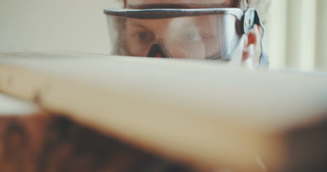 Professional-Carpenter-In-Protective-Glasses-Examining-Wood