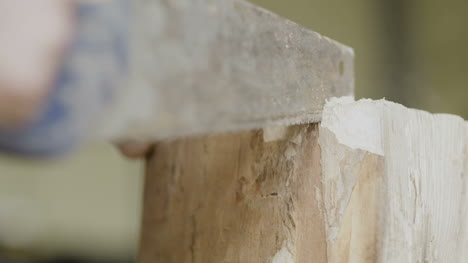 Carpenter-Cutting-Wood-With-Handsaw-In-Workshop