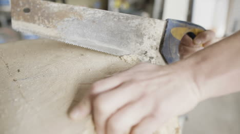 Carpenter-Cutting-Wood-With-Handsaw-In-Workshop-4