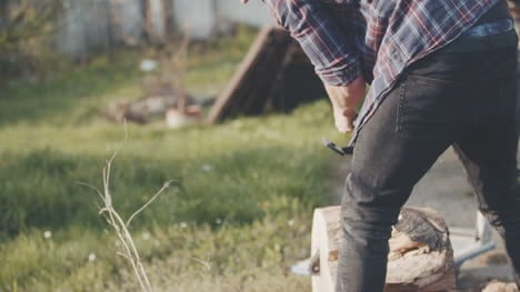 Young-Man-Using-Chainsaw-In-Garden-