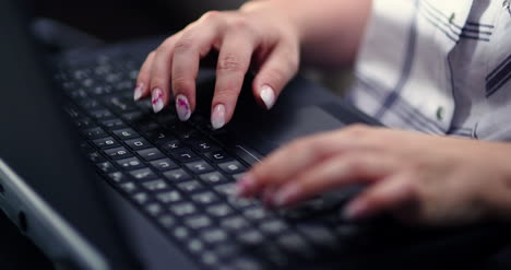 Female-Executive-Working-On-Laptop-At-Workplace