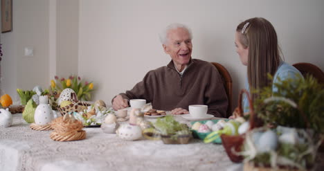 Happy-Easter-Grandfather-And-Granddaughter-Spending-Easter-Together-Talking-At-Home-