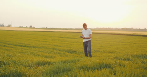 Modern-Young-Farmer-Using-Digital-Tablet-On-Agricultural-Field-