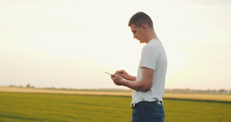 Modern-Young-Farmer-Using-Digital-Tablet-On-Agricultural-Field-1