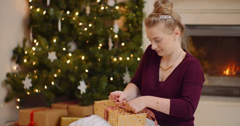 Young-Woman-Tying-Ribbon-On-Christmas-Present-3