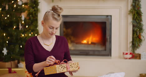 Young-Woman-Holding-Christmas-Present-Against-Fireplace-2