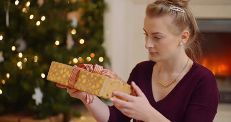 Woman-Shaking-Christmas-Present-Before-Opening-Ribbon