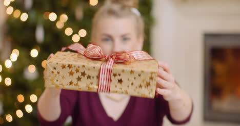 Young-Woman-Showing-Her-Christmas-Gift-At-Home