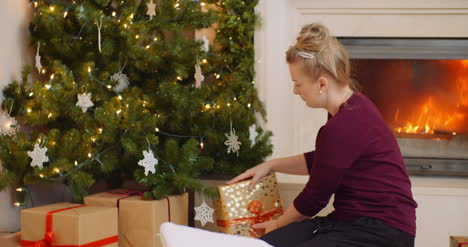 Woman-Positioning-Christmas-Presents-Under-The-Tree
