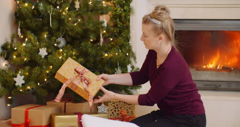 Woman-Positioning-Christmas-Presents-Under-The-Tree-1