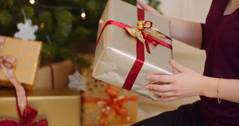 Woman-Holding-Gift-Box-And-Positioning-Under-Christmas-Tree