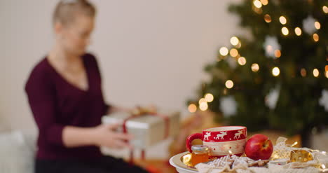 Woman-Holding-Gift-Box-And-Positioning-Under-Christmas-Tree-1