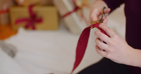 Closeup-Of-Woman-Cutting-Ribbon-From-Roll-With-Scissors
