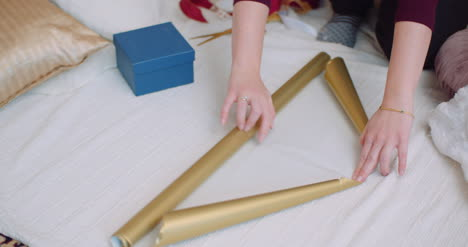 Woman-Wrapping-Christmas-Gift-With-Golden-Paper