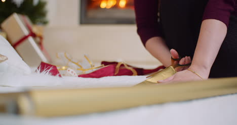 Woman-Cutting-Golden-Wrapping-Paper-At-Home