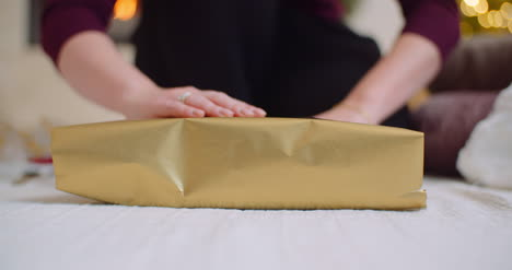 Woman-Applying-Tape-Christmas-Present-With-Golden-Wrapping-Paper