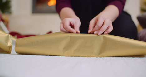 Woman-Applying-Tape-Christmas-Present-With-Golden-Wrapping-Paper-1