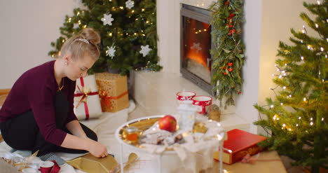 Woman-Wrapping-Christmas-Present-By-Fireplace-At-Home