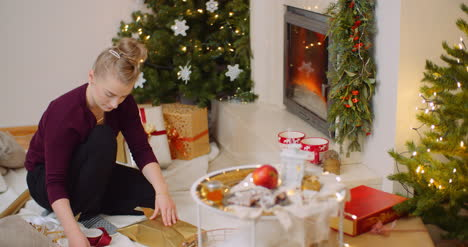 Woman-Wrapping-Christmas-Present-By-Fireplace-At-Home-1