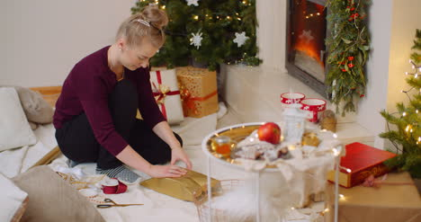 Woman-Wrapping-Christmas-Present-By-Fireplace-At-Home-6