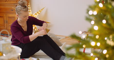 Woman-Wrapping-Christmas-Present-By-Fireplace-At-Home-10