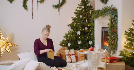 Woman-Wrapping-Christmas-Present-By-Fireplace-At-Home-2