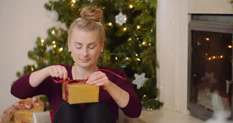 Attractive-Woman-Tying-Ribbon-On-Gift-Box-At-Home-3