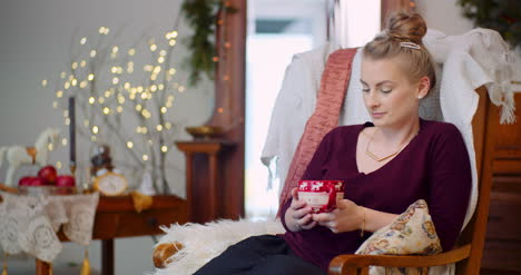 Woman-Relaxing-While-Sitting-With-Coffee-Cup-At-Home