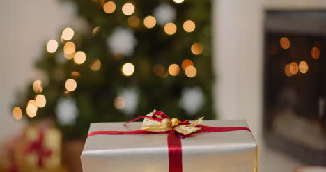 Playful-Woman-Opening-Christmas-Presents-At-Home