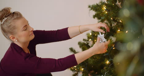 Woman-Decorating-Christmas-Tree-With-Ornaments-And-Lights-2