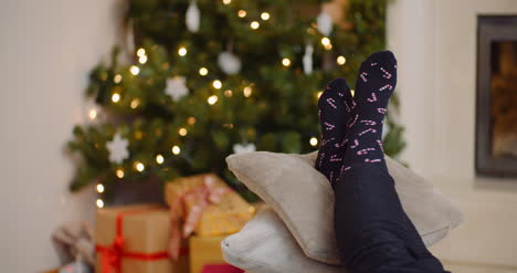 Woman-Relaxing-With-Legs-On-Cushions-Against-Christmas-Tree