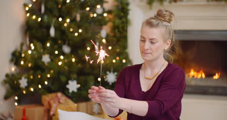 Woman-Igniting-Sparkler-At-Home-During-Christmas-1